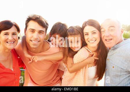 Eltern mit Großeltern, Kindern Huckepack-Fahrt - Stockfoto