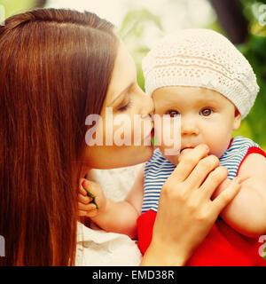 Überrascht Kleinkind Baby Mädchen sitzen auf Mamas Hände, Blick in die Kamera. Mutter das Kind küssen. Entspannen - Stockfoto