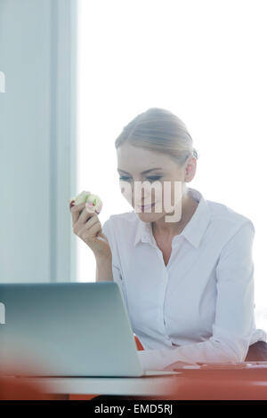 Geschäftsfrau, die sitzen am Schreibtisch zu essen Apfel - Stockfoto