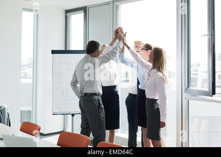 Erfolgreiche Geschäftsleute, die Hände erhebend - Stockfoto