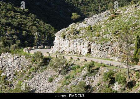 Schmale kurvenreiche asphaltierten Bergstrasse mit niedrigen Stein Barrieren, Ojen, Andalusien, Spanien. - Stockfoto