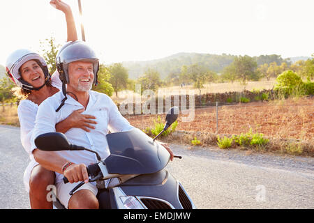 Älteres Paar Reiten Motorroller auf Landstraße - Stockfoto