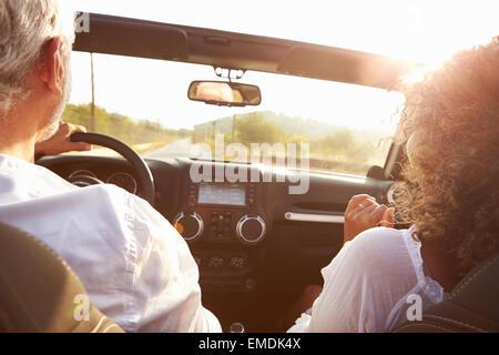 Älteres paar entlang Landstraße im oberen Cabrio fahren - Stockfoto