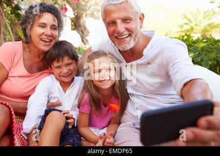 Großeltern mit Enkeln im Garten nehmen Selfie - Stockfoto