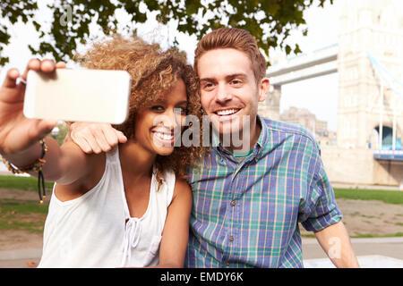 Paar unter Selfie von Tower Bridge In London - Stockfoto