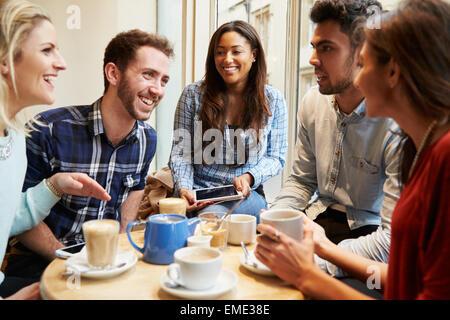 Gruppe von Freunden In Caf' mit digitalen Geräten - Stockfoto