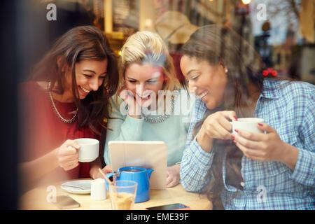 Gruppe von Freundinnen In Caf' mit digitalen Geräten - Stockfoto