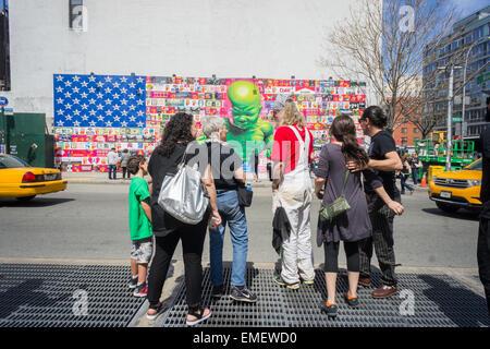 Renommierte Straßenkünstler Ron English, in rot, mit Bewunderern auf seine neue Bowery Wandbild in Soho in New York - Stockfoto