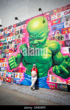 Renommierte Straßenkünstler Ron English posiert vor seinem neuen Bowery Wandbild in Soho in New York Samstag, 18. - Stockfoto