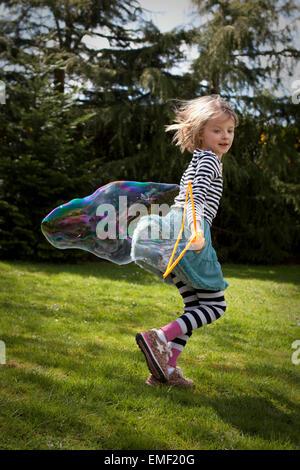 Kind läuft über den Rasen mit riesigen Blase. - Stockfoto