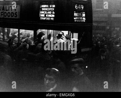 Pendler Schwarm an einem Bus Nr. 649 in Tottenham an einem düsteren Winter-Abend. 21. November 1945 - Stockfoto