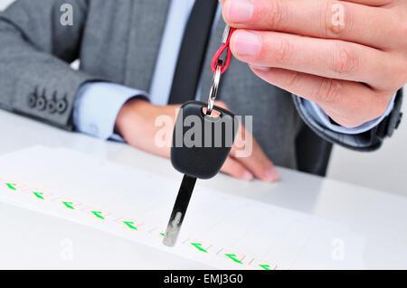 ein junger kaukasischer Mann im grauen Anzug sitzt an seinem Schreibtisch gibt einen Autoschlüssel für dem Betrachter - Stockfoto