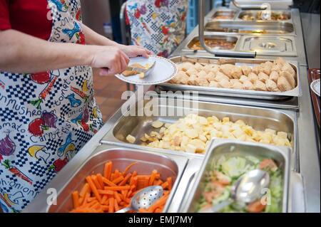 Abendessen-Damen an einer Grundschule UK servieren warmes Abendessen am Mittag - Stockfoto