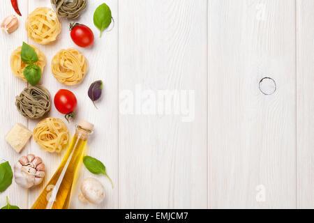 Italienische Küche kochen Zutaten. Nudeln, Tomaten, Basilikum. Draufsicht mit Textfreiraum - Stockfoto