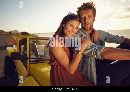 Fröhliches junges Paar sitzt auf der Motorhaube ihres Autos auf einem Roadtrip. Schöne junge Paar zusammen an einem - Stockfoto