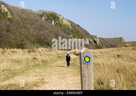 Wanderweg-Zeichen mit Walker auf Wales Coast Path in Oxwich National Nature Reserve auf Gower Halbinsel Swansea - Stockfoto