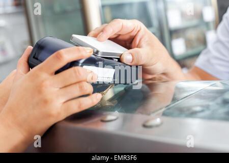 Kunden die Zahlung durch Smartphone in Metzgerei - Stockfoto