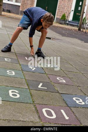 Ein kleiner Junge spielt in Amsterdam Holland die Niederlande Europas Himmel und Hölle - Stockfoto