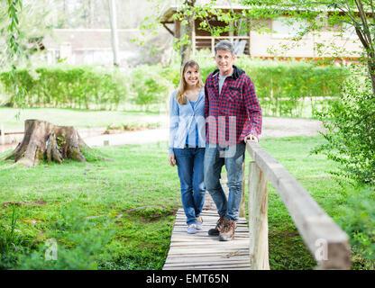 Paare, die auf Holzbrücke - Stockfoto