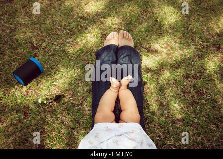 Vogelperspektive Blick auf kleine Baby-sitting auf ihre Mutter Beine auf dem Rasen im Stadtpark. Konzept der Vielfalt, - Stockfoto