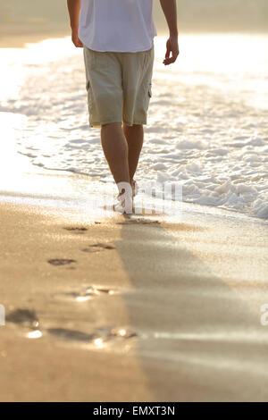 Hintergrundbeleuchtung ein Mann Beine am Strand Spuren - Stockfoto