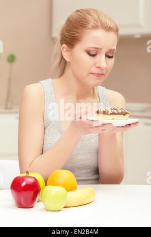 Frau schaut Donut und will es Essen - Stockfoto