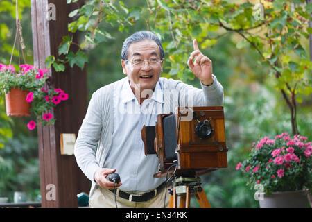 Der alte Mann ist altmodische Kamera verwenden. - Stockfoto