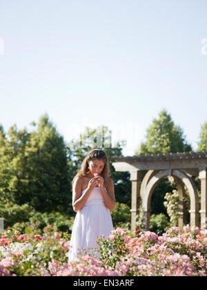 USA, Utah, Lehi, Teenager-Mädchen (16-17) riechenden Blumen im Garten - Stockfoto