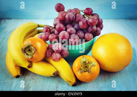 Frisches Obst Hintergrund. Bananen, Trauben, Kaki, Grapefruit. Instagram-Vintage-Effekt. - Stockfoto