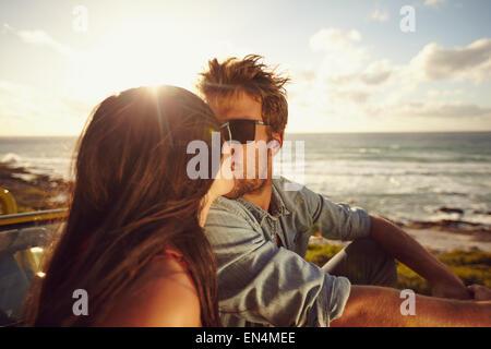 Liebevolle junge Paar küssen am Strand. Junges Liebespaar mit Meer im Hintergrund. Romantisch zu zweit in den Urlaub. - Stockfoto
