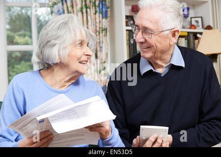 Lächelnd älteres paar Überprüfung persönliche Finanzen - Stockfoto