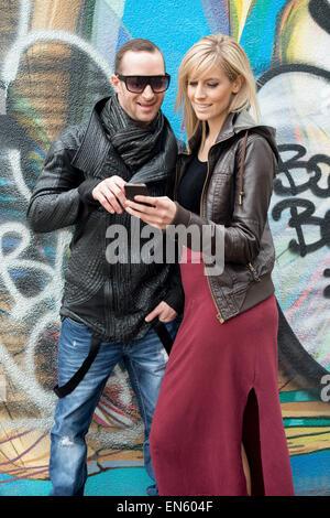 Junges Paar Wand mit Graffiti Handy lächelnd zu betrachten - Stockfoto