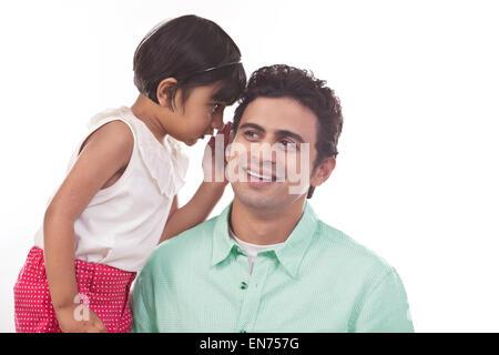 Mädchen, die Väter ins Ohr flüstern - Stockfoto