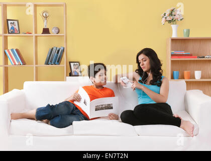 Schwester auf Couch Musikhören während ihres Bruders Blick auf Telefon - Stockfoto