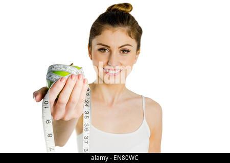 Schlanke Frau hält Apfel und Maßband - Stockfoto