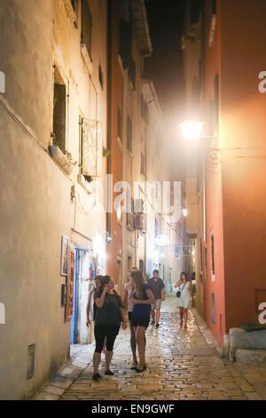 Passanten in einer engen Straße in der Nacht in Rovinj, Kroatien - Stockfoto