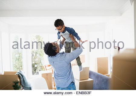 Umzugskartons, um Vater Sohn heben - Stockfoto