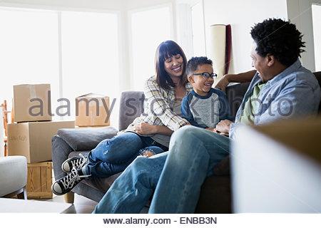 Umzugskartons rund um Familie entspannend auf sofa - Stockfoto