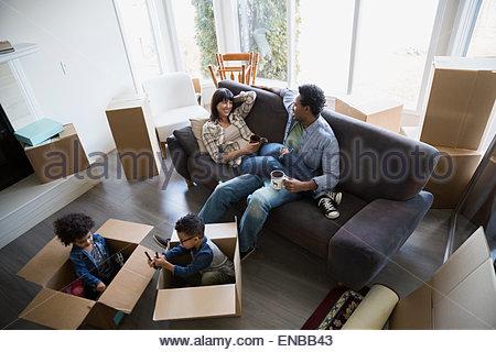 Umzugskartons, die rund um die Familie im Wohnzimmer entspannen - Stockfoto