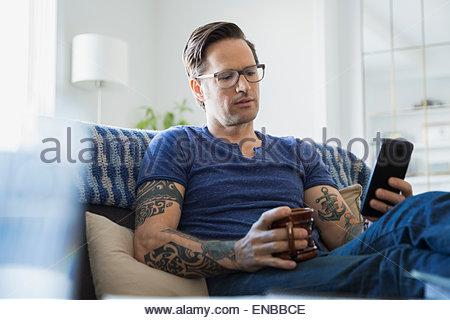 Mann, Tätowierungen und Kaffee SMS im Wohnzimmer - Stockfoto