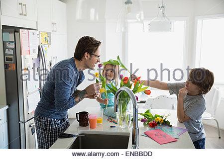 Vater und Kinder, die Vermittlung von Tulip Bouquet in Küche - Stockfoto