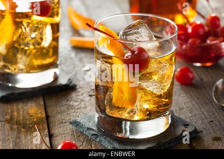 Hausgemachte Old Fashioned Cocktail mit Kirschen und Orangenschale - Stockfoto