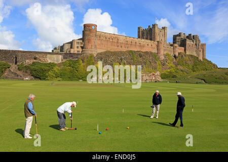 Vier Männer spielen Krocket auf dem Dorfplatz in von Bamburgh Castle, Bamburgh, Northumberland, England, UK - Stockfoto