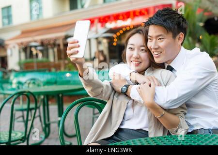Koreanische paar Handy fotografieren im Straßencafé - Stockfoto