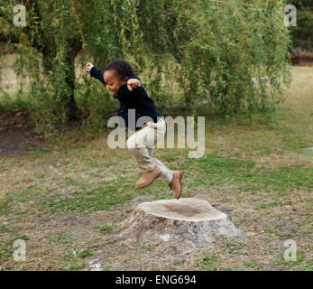 African American Boy Spielen auf stumpf im park - Stockfoto