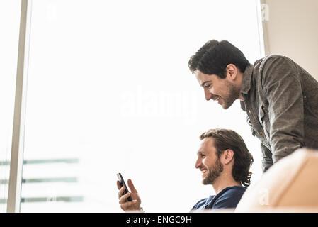 Zwei Geschäftsleute mit Blick auf ein Smartphone und lächelnd. - Stockfoto
