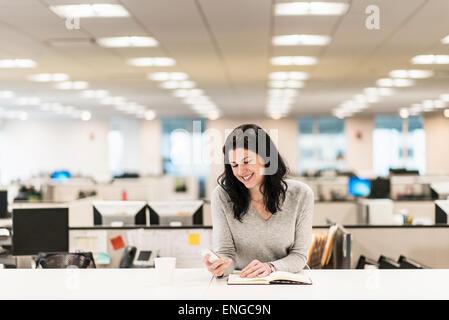 Eine Frau sitzt an einem Schreibtisch mit der Hand auf ein offenes Buch, überprüfen ihr Smartphone. - Stockfoto