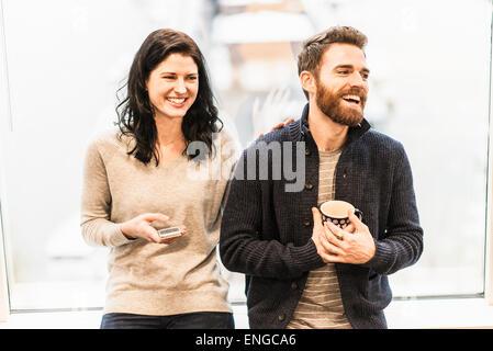 Eine Business-Frau sitzt an einem Fenster hält ein smart Phone, Gespräch mit einem Mann hält eine Kaffeetasse. - Stockfoto