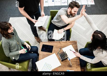 Vier Personen sitzen an einem Tisch, Kollegen bei einer Planung treffen hohe Fiveing einander. - Stockfoto