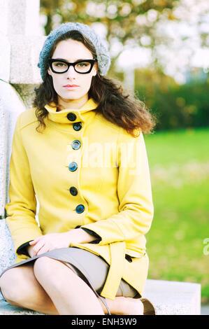 Mode-Porträt im Park der jungen Frau in Gläser und gelben Mantel - Stockfoto